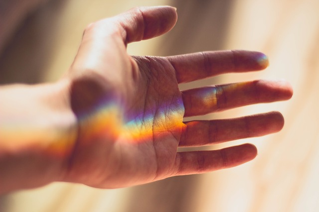 A hand in warm sunlight, reaching out, with a prism reflecting a faint rainbow across the palm.