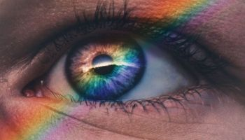 Picture of a person's eye close up with a rainbow going over it in a diagonal line. The iris of the eye blends into the color of the rainbow overlaying it.