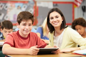 Student around 10 years old in a classroom using a tablet sitting next to a teacher. They are both looking at the camera.