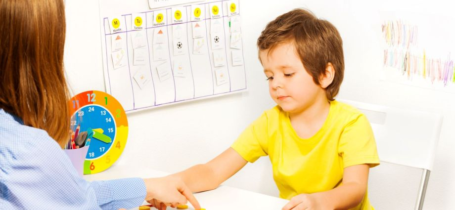 Therapist white woman pointing to an object on a table and a white boy pointing to another object on the table.