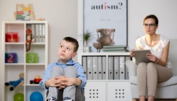 """A white boy looking up and to the right looking concerned, sitting on the floor with his hands around his knees/legs, and a therapist sitting in a chair behind him staring at him with a clipboard. The poster next to the therapist says """"autism?"""""""
