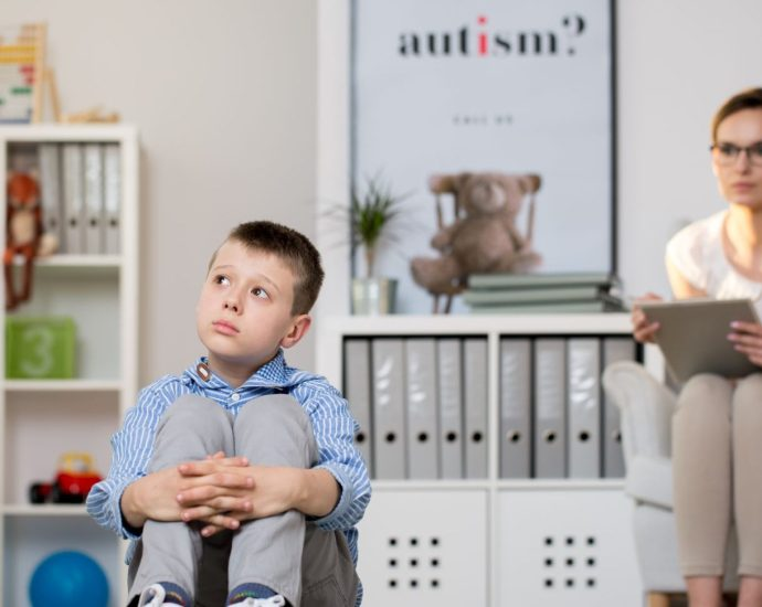 "A white boy looking up and to the right looking concerned, sitting on the floor with his hands around his knees/legs, and a therapist sitting in a chair behind him staring at him with a clipboard. The poster next to the therapist says ""autism?"""