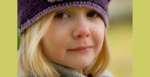 girl looking into the camera with tears rolling down her face, crying