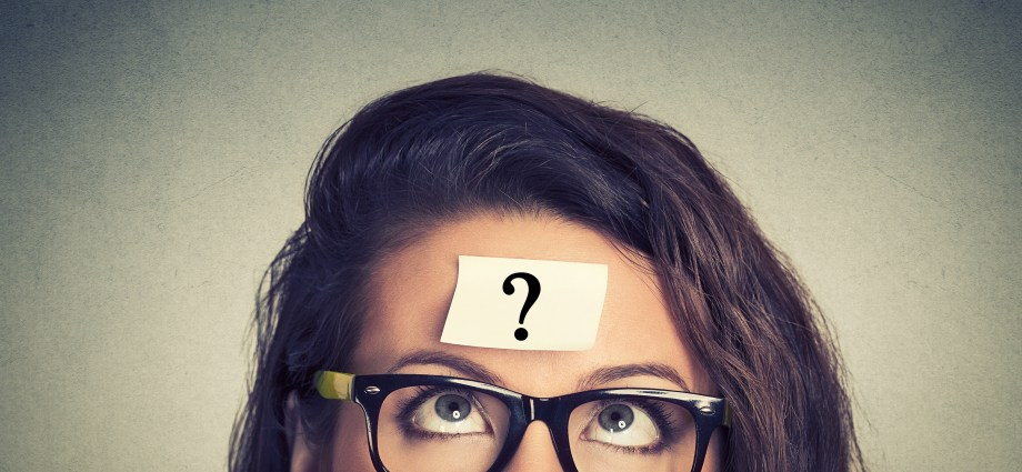 A woman with a question mark post it note on her forehead, while looking up at it.