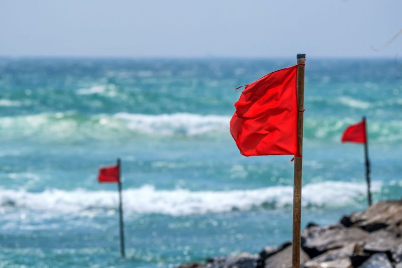 Red flags in rocks with the ocean right next to it.