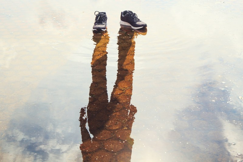 Shoes on water, with only the sillhouette of a person standing in the reflection.