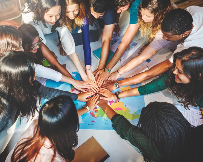 A group of teenage students of different skin colours and genders are piling their hands on top of each others' in a show of solidarity and community.