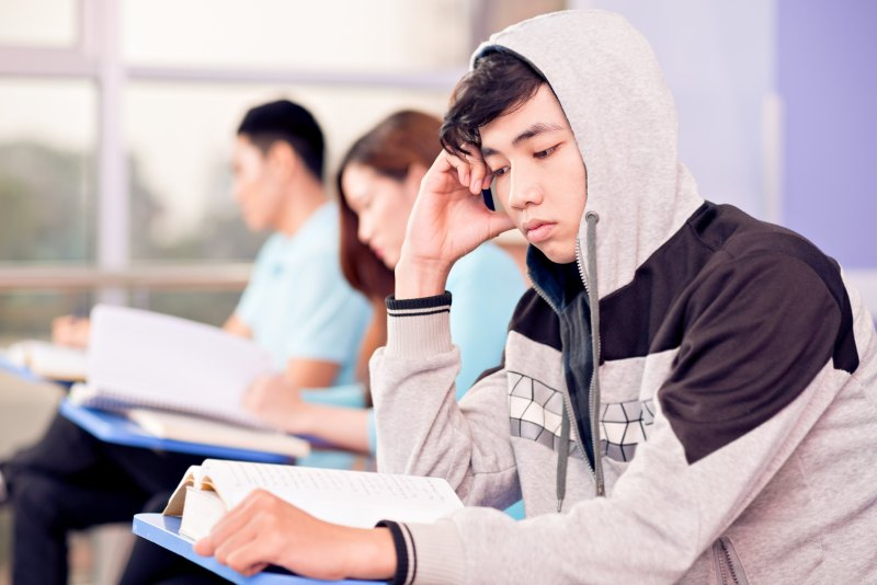 Asian teenager reading a book in a classroom with his hood up leaning on his hand.