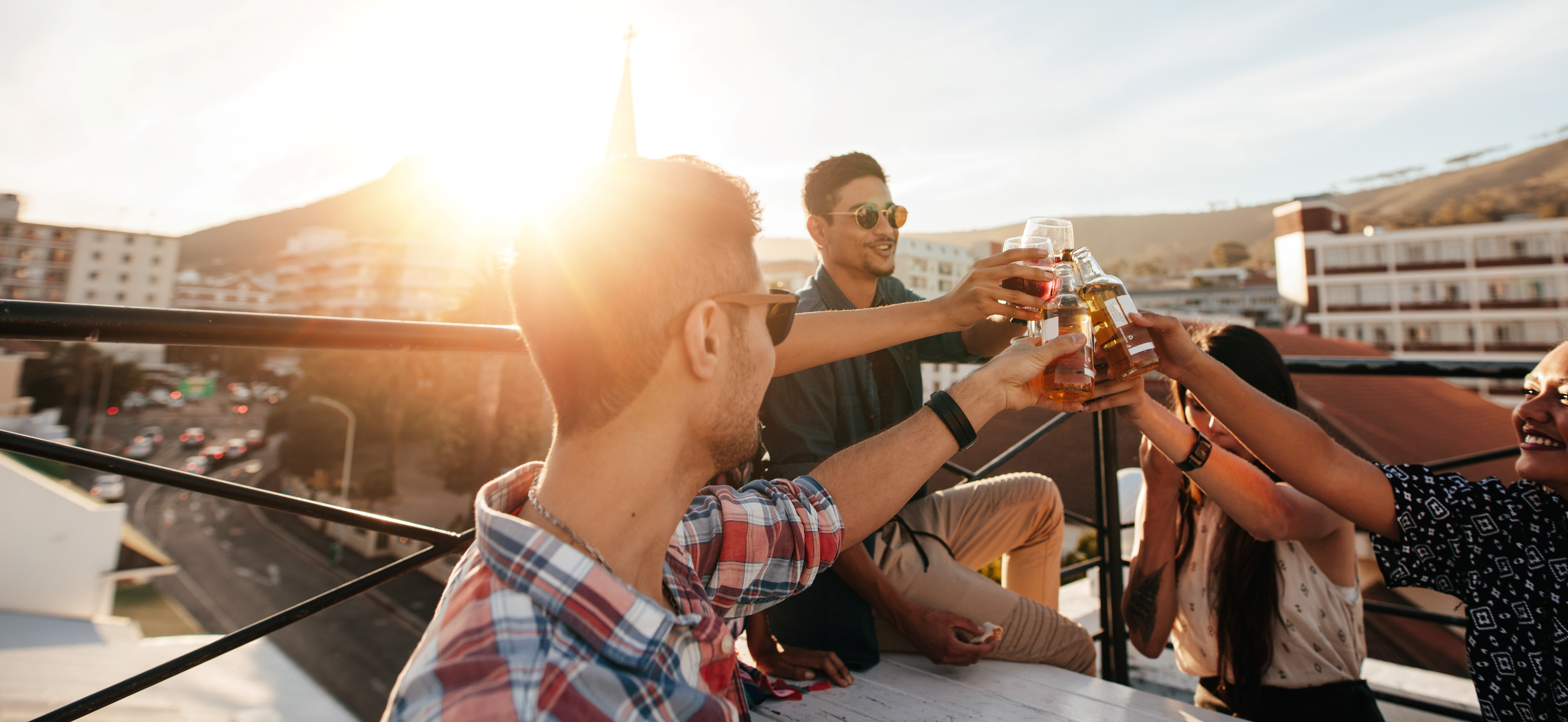 Friends are doing a toast on a rooftop. The autistic friend here would not be having a drink because he is a recovering addict.