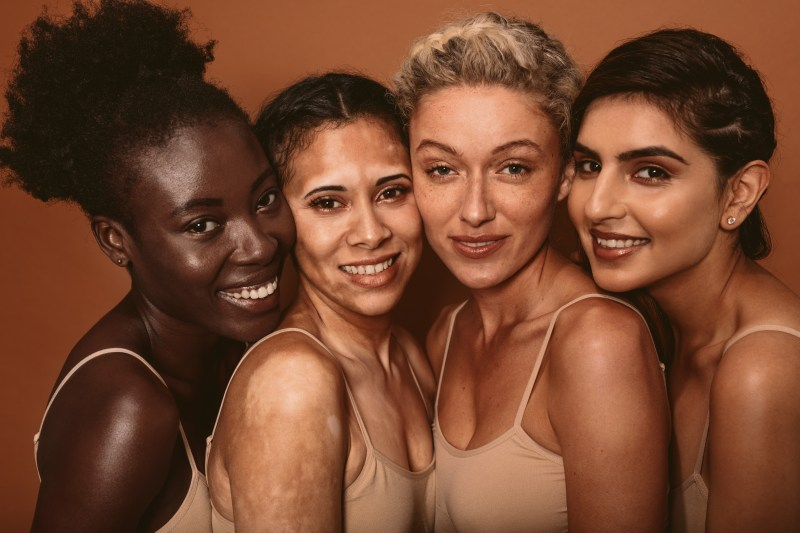 Four women with different racial backgrounds, ages, skin tones smile and stand together., and