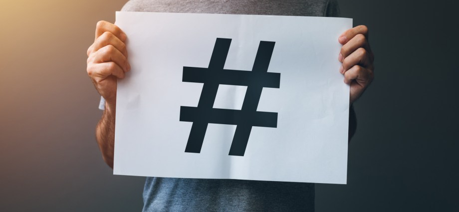Man holding a hashtag sign to signify that he is a neurolurker or undiagnosed or questioning autistic person