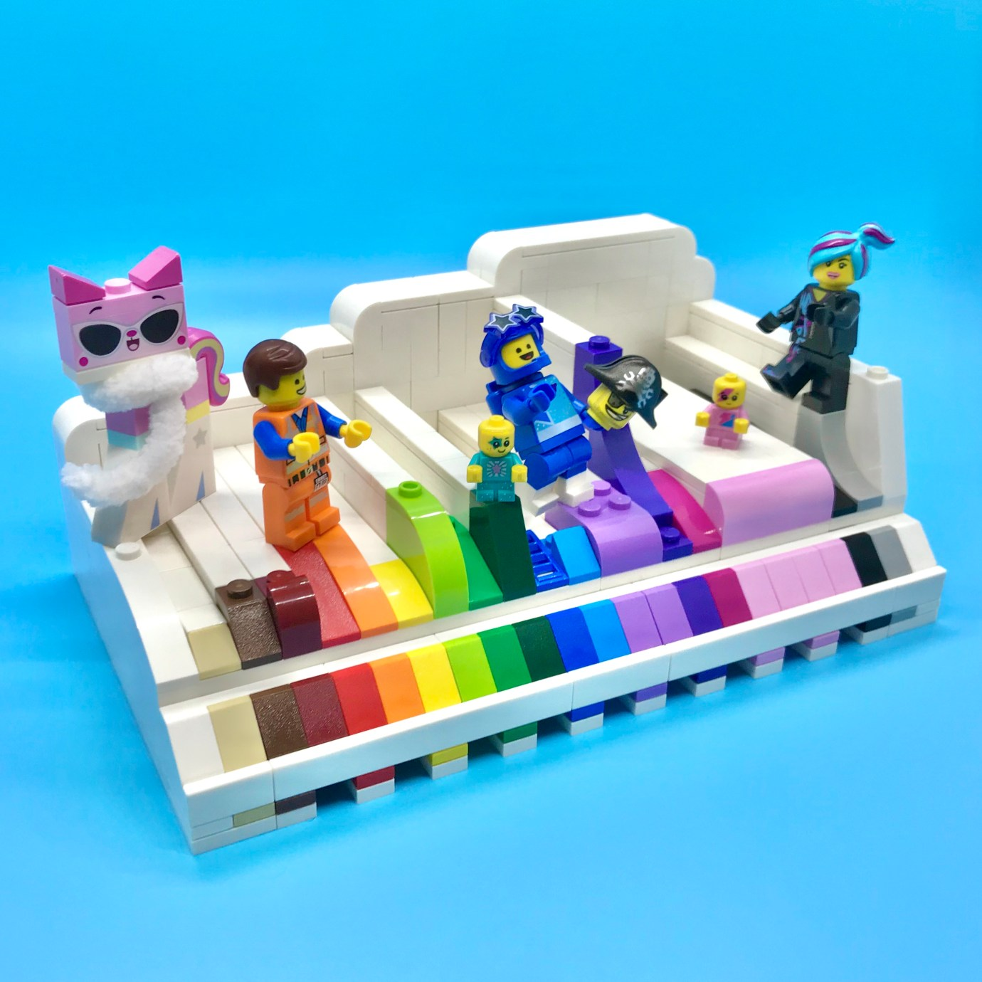 A group of LEGO minifigures dance on a color coded LEGO slope display.