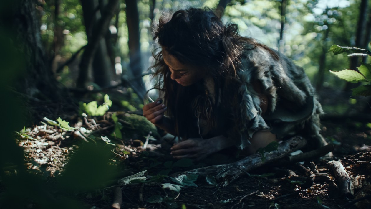 Prehistoric Cave Woman Hunter-Gatherer Searches for Nuts and Berries in the Forest. Primitive Neanderthal Woman Finding Food in the Sunny Forest