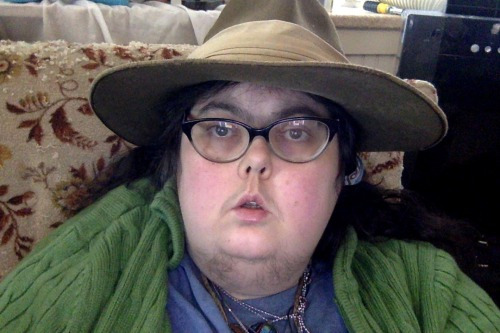 Mel Baggs - a heavy set person, wearing glasses and a wide brimmed hat, looking into the camera.