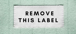 """There is a white label that reads """"remove this label"""" on a light blue fabric. It is meant to symbolize the labels of high low functioning autistic person with autism on the autism spectrum. Also, it is referencing the labels of disorder, mental illness, and disability as they apply to autism asperger's aspie."""