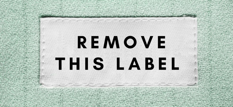 "There is a white label that reads ""remove this label"" on a light blue fabric. It is meant to symbolize the labels of high low functioning autistic person with autism on the autism spectrum. Also, it is referencing the labels of disorder, mental illness, and disability as they apply to autism asperger's aspie."