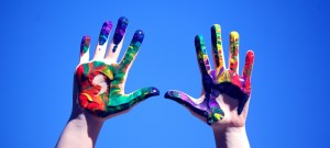 two hands in the air, presumably hands of an autistic kid with autism on the spectrum, to celebrate neurodiversity. they are covered with colorful paints