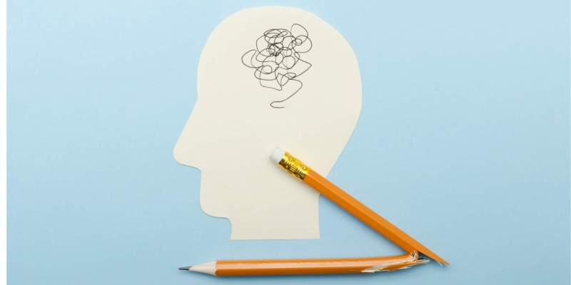 a cut-out of a head with scribbles for a brain and a broken pencil to demonstrate autism autistic catatonia