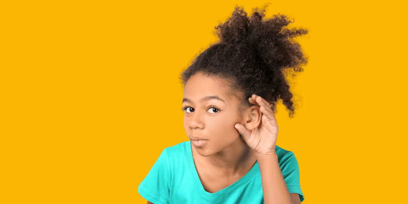 young Black girl with curly hair in pony tail cupping her hand to her ear