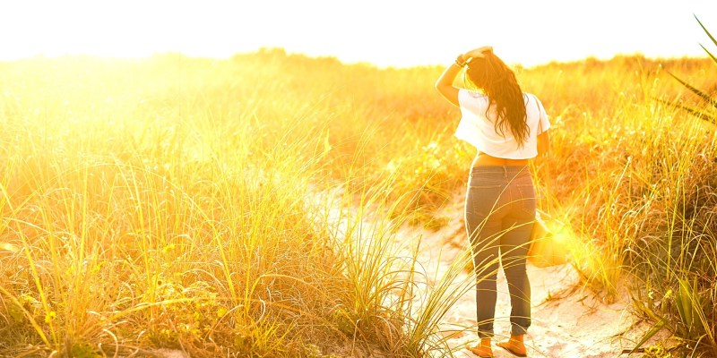 A woman is walking through a field. She has her hand on her hair and the sun is casting a golden hue on the tall grass