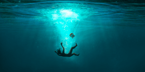 a silhoette of a man is falling into deep water and is several feet below the surface. Between him and the surface is a lyre.