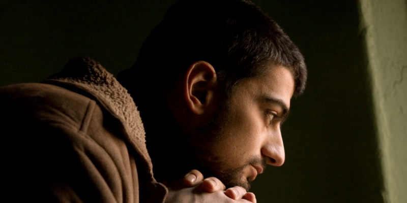 an indian american man looks out a window. he appears to be in deep thought