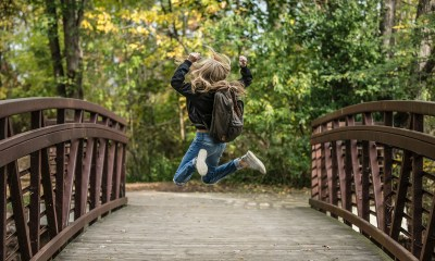happy child jumping on a bridge