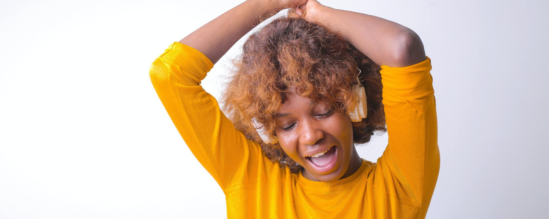 A black person with feminine presentation is in a yellow shirt with medium hair wearing headphones and singing to themselves with their arms over their head