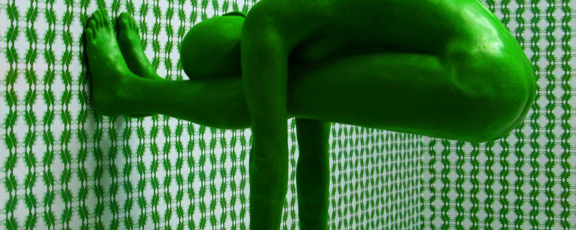 A Green man is bent in an unnatural state while hanging akwardly off a wall from his feet