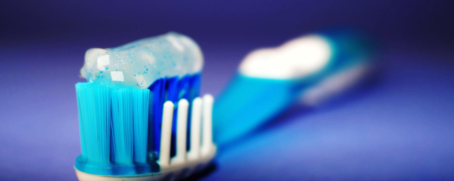 closeup of a blue and white toothbrush on blue backdrop