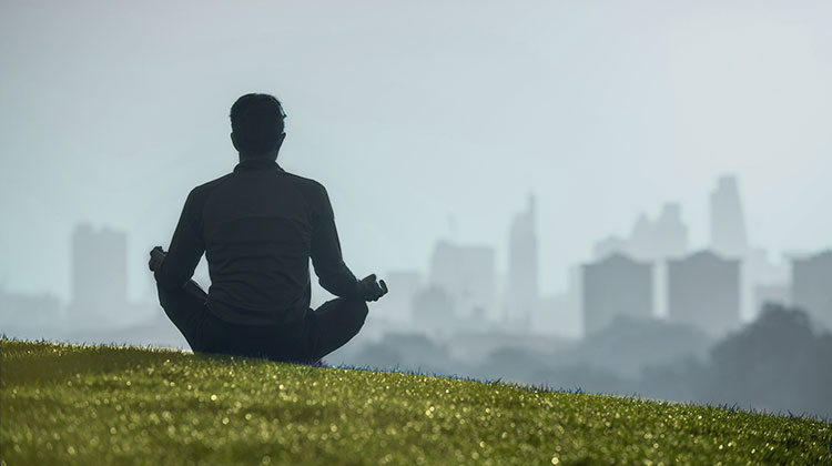 Silhouette of a man sitting in the lotus position meditating on grassy hill in front of the London city skyline