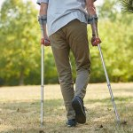 Man walking with crutches wearing step counter