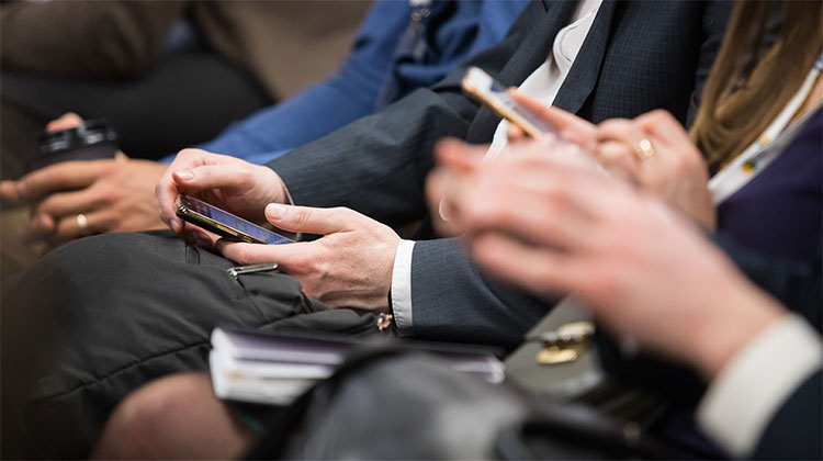 Attendees using mobile phones during conference session