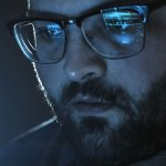 Closeup of man's face with reflection from computer in his glasses