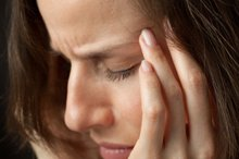The image shows a woman rubbing her head as though she has a migraine.