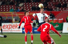 The image shows a football player going to 'header' a ball during a Poland versus US friendly soccer game.