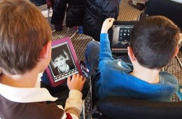 The image shows children using an ipad.