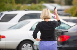 The image shows a woman clicking her keys, looking for her car.