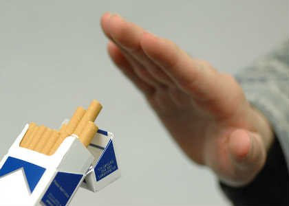 The image shows a person refusing a cigarette from a packet.