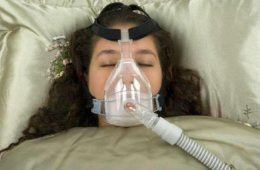 The image shows a woman sleeping with a CPAP machine on.