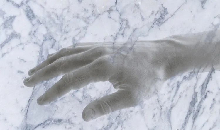 This image shows a hand coming out of a slab of marble.
