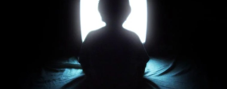 The image shows a child sitting in front of a TV set. The image is dark, as if to imply this image is taken late at night.