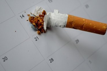The image shows a stubbed out cigarette on a calender.