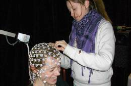 The image shows the researcher putting the EEG headset on a study participant.