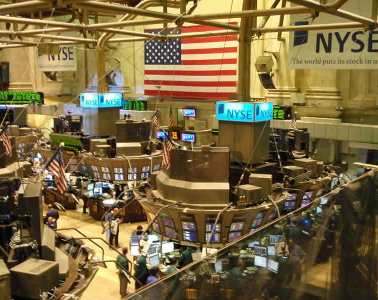 The image shows the trading floor in the New York Stock Exchange.
