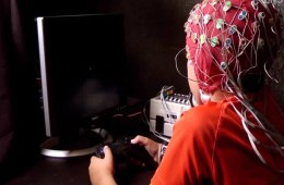 The image shows a still from the video. A little boy is being tested and is wearing an EEG cap.