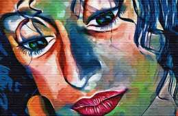 The image shows a colorful painting of a woman's face with no expression.