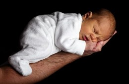 This image shows a baby sleeping in its father's arms.