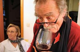 This image shows an older man tasting a glass of wine.