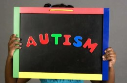 This image shows a child holding up a chalk board with the word Autism written on it.